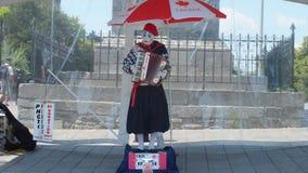Boots straatuitvoerder na die een harmonika spelen stock afbeeldingen