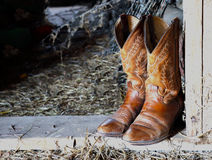 Boots and straw in the barn. An old pair of cowboy boots in a straw strewn barn stock photography