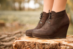 Boots on stump. Closeup of female brown boots outdoors on stump Stock Photo