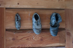 Boots. Three old boots hanging from a wooden door Stock Photo