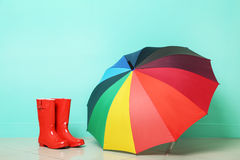 Boots with umbrella. Red boots with umbrella on green background Stock Image