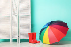 Boots with umbrella. Red boots with umbrella near wooden folding screen on a green background Royalty Free Stock Photo