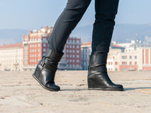 Boots of a walking woman. A woman with black boots walking on a street in Trieste Stock Photos