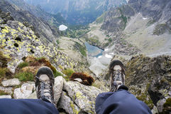 Boots of a woman sitting on the edge of a cliff in Stock Photos