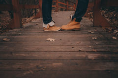 Boots of young couple walking outdoor on wooden bridge in autumn Royalty Free Stock Images
