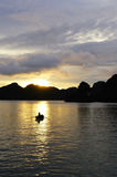 Bootsfrau gegen Sonnenuntergang in Halong-Bucht Stockfoto
