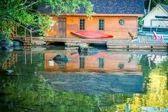 Bootshaus mit rotem Kanu und Adirondak-Stühle auf einem Dock lizenzfreie stockbilder