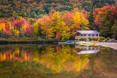 Bootshaus und Fallfarben, die in Echo Lake, in Franconia sich reflektieren lizenzfreie stockfotos