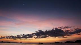 Bootsilhouet die de oceaan kruisen bij het vallen van de avond met oranje hemel Stock Foto