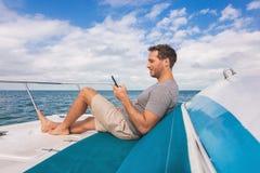 Bootsmann unter Verwendung des Handys, der auf Satelliteninternet bei der Entspannung auf Plattform von Yachtluxus simst stockbilder
