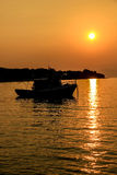 Bootsschattenbild im orange Sonnenuntergang Stockbild