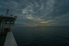 Bootssegeln am bewölkten stürmischen Tag während des schönen Sonnenuntergangs Lizenzfreies Stockfoto