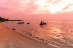 Bootssegeln im Meer mit einem schönen Satzsonnenuntergang hinten Lizenzfreie Stockbilder