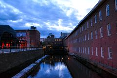 Boott Mills. Clouds reflect off the Merrimack Wasteway between Boarding House Park  and Boott Mills in Downtown Lowell, Massachusetts Royalty Free Stock Photography