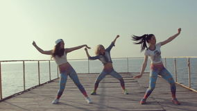 Booty dance by girls teenager on a wooden berth at the sea