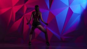 Booty danse with girl in shorts on bright graphic background. Slow motion stock video