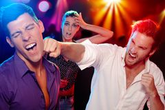 Bopping in the nightclub. Two young men bopping in the nightclub for a women, who is looking worried at background Stock Image