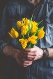 Boquet van gele tulpen in handen Royalty-vrije Stock Foto's