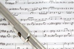 Boquilla de la flauta en partitura Imagen de archivo libre de regalías