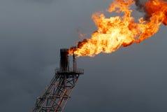 Boquilla y fuego del auge de la flama en plataforma petrolera costera Imagen de archivo