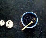 borówka w błękitnym pucharze na rocznika metalu ośniedziałym tle Pojęcie organicznie jagody fotografia stock