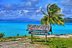 Bora Bora airport. HDR image of Bora Bora airport sign. Beautiful palm and blue sea at the background. French Polynesia, South Pacific Ocean stock image