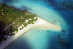 Bora Bora Island. Aerial View of Bora Bora beach resort with coral reef, palm trees and and small boat Stock Photos