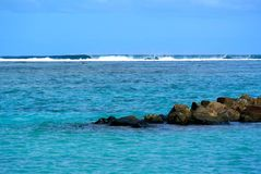 Ocean rocks with waves. Bora bora lagoon waves crashing with beach rocks extending into water from the shore royalty free stock images