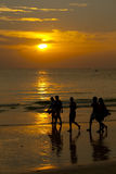 Boracay beach, Philippines. Group of friends strolling along the sea shore, admiring the sunset stock image