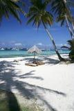 Boracay island blue sky white beach philippines. Simple sun loungers amidst palm trees and white sand beach of popular boracay island in the philippines Royalty Free Stock Photos