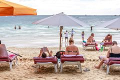 People on sunbed reading book under parasol at tropical Boracay. BORACAY ISLAND, PHILIPPINES - November 17, 2017 : People on sunbed reading book under parasol at Royalty Free Stock Photos