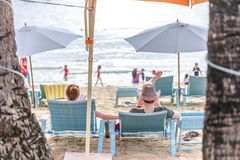 People on sunbed reading book under parasol at tropical Boracay. BORACAY ISLAND, PHILIPPINES - November 17, 2017 : People on sunbed reading book under parasol at Royalty Free Stock Images