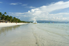 Boracay island white beach paraw philippines. Palms trees and white sand beach of beautiful boracay island in the philippines with traditional paraw sailing boat Stock Images