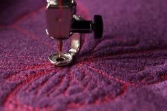 borboleta cor-de-rosa como um bordado em andamento em lãs fervidas roxas imagens de stock