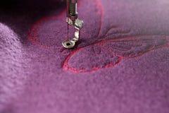 borboleta cor-de-rosa que está sendo costurada em lãs fervidas roxas foto de stock