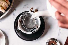 A borboleta quente Pea Blueberry Tea serviu derramando da caneca através do infuser de aço inoxidável do filtro do chá no copo do fotos de stock