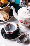 A borboleta quente Pea Blueberry Tea serviu derramando da caneca através do infuser de aço inoxidável do filtro do chá no copo do fotografia de stock royalty free