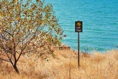 Bord de falaise de panneau d'avertissement avec un arbre Photographie stock libre de droits