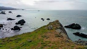 Bord de falaises se dirigeant dangereusement au-dessus du rivage rocheux d'océan Photos libres de droits