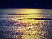 Bord de glace Le bord de l'eau de jaune orange a dégelé de dessous une banquise blanche brillante Images libres de droits