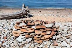 Bord de la mer avec l'endroit de feu de camp des cailloux ronds et de la plage sablonneuse avec le rondin en bois Image stock