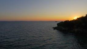 Bord de la mer avec les maisons et les treees résidentiels au coucher du soleil banque de vidéos