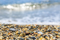 Bord de la mer avec les vagues et le Pebble Beach de tache floue Images libres de droits
