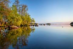 Bord de lac calme au coucher du soleil Image libre de droits