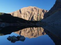 Bord de lac rocheux avec la montagne et le ciel Photographie stock