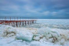 Bord de mer congelé par hiver et le vieux pilier Photographie stock