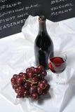 Bord en wijn met druiven Stock Afbeeldingen