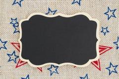 Bord met de rode en blauwe sterren van de V.S. op juteachtergrond Royalty-vrije Stock Afbeelding
