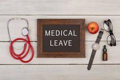 bord met tekst & x22; Medische leave& x22; , oogglazen, horloge en stethoscoop royalty-vrije stock fotografie