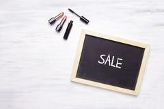 Bord met Verkoop op het wordt geschreven, en cosmetischee producten op whi die Stock Foto